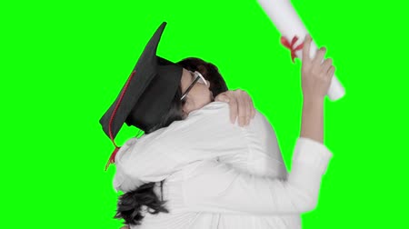 promoce : Slow motion of excited woman in graduation hat hugging her boyfriend while holding a diploma in the studio. Shot with green screen background