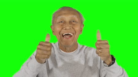 good looking guy : Happy senior man smiling and showing thumbs up in the studio. Shot in 4k resolution with green screen background