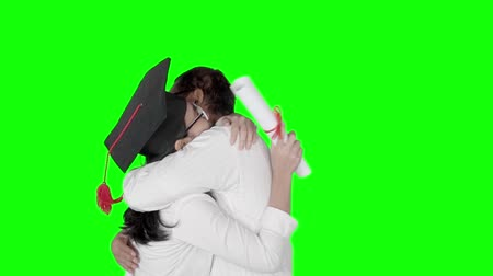 promoce : Slow motion of happy woman in graduation cap hugging her boyfriend while holding a diploma. Shot in the studio with green screen background Dostupné videozáznamy