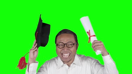 grãos : Slow motion of joyful man celebrating his graduation while holding a graduation cap and a diploma. Shot in the studio with green screen background Stock Footage