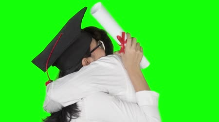 promoce : Slow motion of cheerful man hugging and congratulate his girlfriend in graduation cap and holding a diploma. Shot in the studio with green screen background