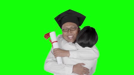 bakalář : Slow motion of young man in graduation cap and holding a diploma hugging his girlfriend. Shot in the studio with green screen background Dostupné videozáznamy
