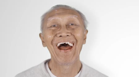 implantaat : Slow motion of cheerful senior man with dentures laughing in the studio, isolated on white background