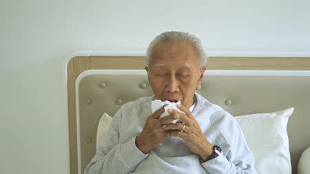 influenza : Sick old man sneezing with a tissue while sitting on the bed in the bedroom. Shot in 4k resolution Stock Footage