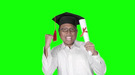grãos : Slow motion of happy young man celebrating his graduation and success while wearing a graduation hat and holding a diploma. Shot in the studio with green screen background