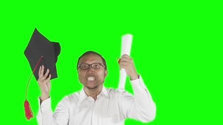 promoce : Slow motion of successful man celebrating his graduation while holding a graduation cap and a diploma in the studio. Shot with green screen background