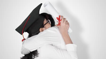 promoce : Slow motion of young woman hugging her boyfriend while celebrating her graduation and wearing a graduation cap. Isolated on white background