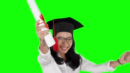 promoce : Slow motion of cheerful woman celebrating her graduation and success while wearing graduation cap and holding a diploma in the studio. Shot with green screen background Dostupné videozáznamy