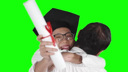 promoce : Slow motion of happy young woman hugging her boyfriend while wearing graduation cap and holding a diploma. Shot in the studio with green screen background