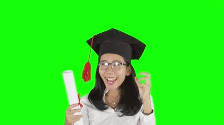 promoce : Slow motion of a young Asian woman in mortarboard celebrating her graduation while holding a diploma. Shot in studio with green screen background