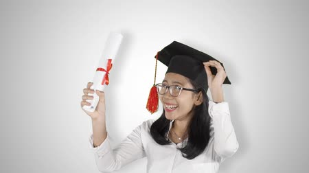 диплом : Slow motion of cheerful Asian woman celebrating her graduation and success while holding a diploma and wearing a graduation cap in the studio. Isolated on white background
