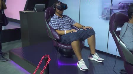 convenção : JAKARTA, Indonesia - July 23, 2019: Male visitor trying VR glasses simulator in GAIKINDO Indonesia International Auto Show (GIIAS) 2019 at Indonesia Convention Exhibition (ICE)