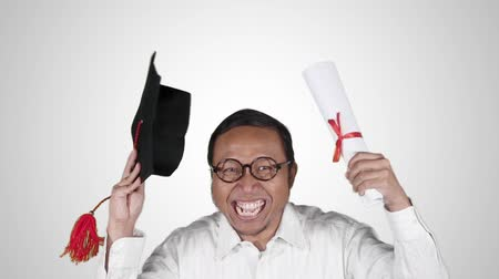 promoce : Slow motion of joyful man celebrate graduation and expressing his success while holding a graduation cap and diploma, isolated on white background