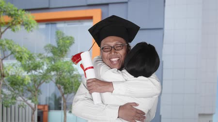 promoce : Slow motion of man hugging a woman while wearing a graduation cap and holding a diploma during celebrate graduation in university yard