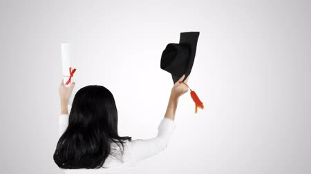 promoce : Rear view of young woman celebrating her graduation while raising a graduation cap and diploma in the studio, isolated on white background. Shot in 4k resolution