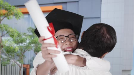 promoce : Slow motion of woman embracing a man while wearing a graduation cap and holding a diploma during celebrate graduation