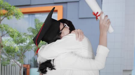 promoce : Slow motion of young woman hugging a man while wearing a graduation hat and holding a diploma during celebrate graduation in university yard Dostupné videozáznamy