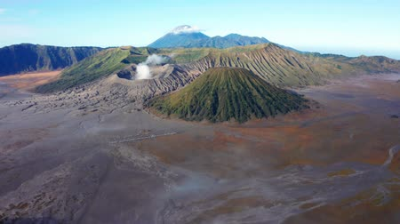 erupção : Beautiful aerial landscape of Mount Bromo volcano peak with volcanic gas and desert, East Java, Indonesia. Shot in 4k resolution from a drone flying forwards