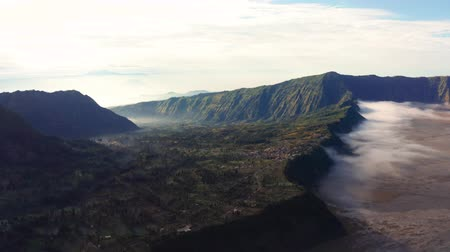 erupção : Beautiful aerial view of Mount Bromo volcano with smoke on misty morning, East Java, Indonesia. Shot in 4k resolution from a drone flying from left to right Vídeos
