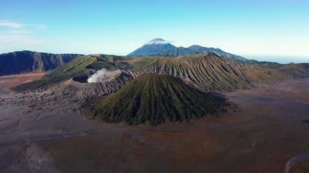 kráter : Beautiful aerial view of Mount Bromo volcano peak with volcanic desert and gas, East Java, Indonesia. Shot in 4k resolution from a drone flying forwards Stock mozgókép