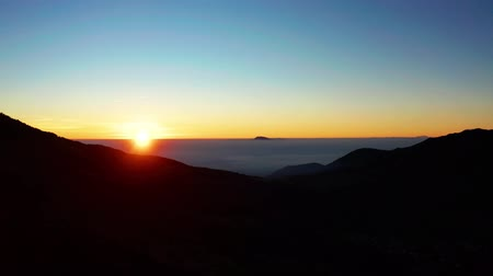 forwards : Beautiful aerial view of sunrise time with orange sunlight and silhouette of highland in Dieng Plateau, Wonosobo, Central Java. Shot in 4k resolution from a drone flying forwards