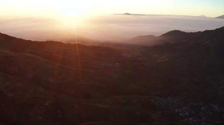 плато : Beautiful aerial view of sunrise with silhouette of valley in Dieng Plateau, Wonosobo, Central Java, Indonesia. Shot in 4k resolution from a drone flying backwards