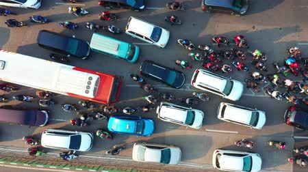 bottleneck : JAKARTA, Indonesia - July 30, 2019: Top down view cars and motorcycle moving on traffic jam at rush hour in Jakarta city. Shot in 4k resolution from a drone flying upwards