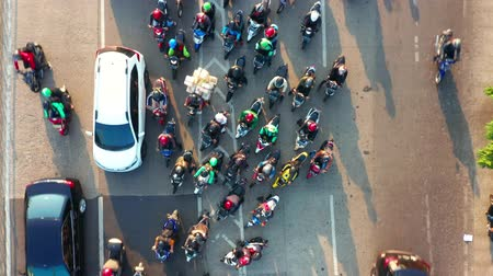 bottleneck : JAKARTA, Indonesia - July 30, 2019: Top down view of crowded motorcycle and cars moving at traffic jam on highway. Shot in 4k resolution from a drone flying forwards
