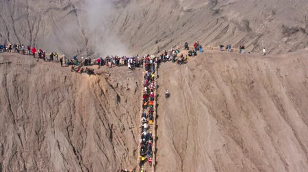 forwards : EAST JAVA, Indonesia - July 30, 2019: Aerial view of crowded tourists climbing stairs and enjoying Mount Bromo crater landscape. Shot in 4k resolution from a drone flying forwards