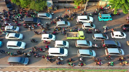 bottleneck : JAKARTA, Indonesia - July 30, 2019: Aerial landscape of motorcycle and cars moving at the traffic jam on highway. Shot in 4k resolution from a drone flying from right to left