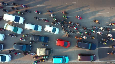 bottleneck : JAKARTA, Indonesia - July 30, 2019: Top down view of crowded motorcycle and cars moving on the road at rush hour in Jakarta downtown. Shot in 4k resolution