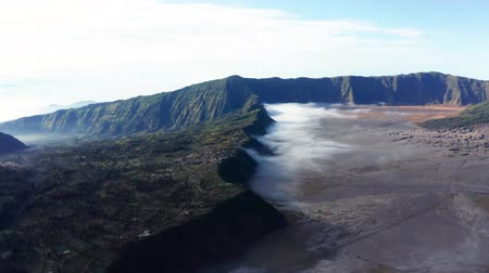 кальдера : Beautiful aerial view of Mount Bromo during misty morning with fog, East Java, Indonesia. Shot in 4k resolution from a drone flying forwards Стоковые видеозаписи