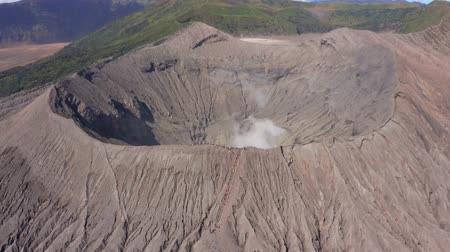 посетитель : EAST JAVA, Indonesia - July 30, 2019: Beautiful aerial view of Mount Bromo volcano crater and crowded tourists. Shot in 4k resolution from a drone flying backwards Стоковые видеозаписи