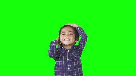 arrumado : Attractive little boy posing in the studio while tidy up his hair. Shot in 4k resolution with green screen background