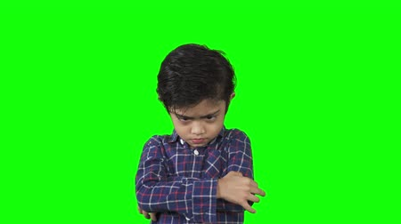 carrancudo : Cute little boy looks cranky while crossed his arms in the studio. Shot in 4k resolution with green screen background