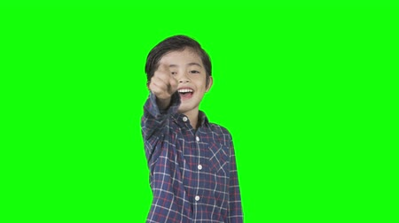 perverso : Little boy looks mocking someone by laughing and pointing at the camera in the studio. Shot in 4k resolution with green screen background