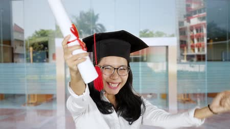 promoce : Slow motion of cheerful woman expressing her success while celebrating graduation with a diploma and graduation hat at university yard.