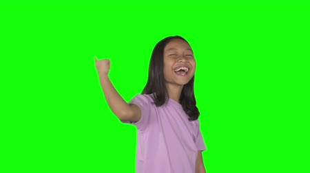 moqueries : Little girl laughing and pointing at the camera looks bullying or mocking someone. Shot in 4k resolution with green screen background