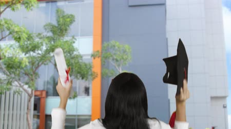 mortarboard : Back view of happy unknown woman celebrating her graduation while holding a graduation cap and diploma at university yard. Shot in 4k resolution