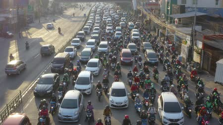 backwards : JAKARTA, Indonesia - August 07, 2019: Aerial view of crowded cars and motorcycle moving on lane in traffic jam at highway. Shot in 4k resolution from a drone flying backwards