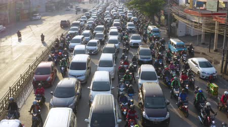 bottleneck : JAKARTA, Indonesia - August 07, 2019: Aerial view of crowded vehicles moving on its lane slowly during traffic jam. Shot in 4k resolution from a drone flying forwards