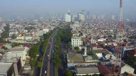 bottleneck : JAKARTA, Indonesia - August 07, 2019: Aerial Jakarta cityscape with crowded traffic at the morning on highway. Shot in 4k resolution from a drone flying down Stock Footage