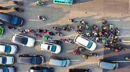 bottleneck : JAKARTA, Indonesia - August 07, 2019: Top down time lapse view of crowded cars and motorcycle moving on traffic congestion during rush hour. Shot in 4k resolution from a drone