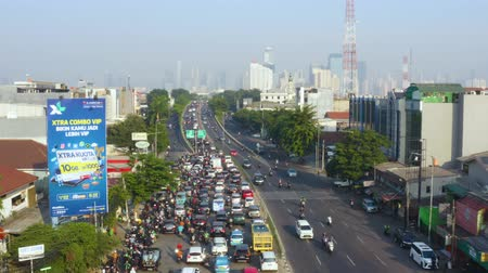 bottleneck : JAKARTA, Indonesia - August 07, 2019: Aerial view of traffic congestion on the morning with chaotic vehicles scramble the road. Shot in 4k resolution from a drone flying forwards