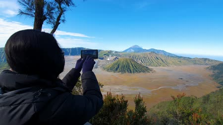 erupção : Silhouette of woman taking picture of Mount Bromo with a mobile phone in East Java, Indonesia. Shot in 4k resolution Vídeos