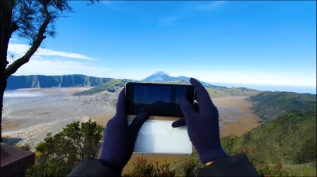 erupção : Silhouette of woman hand taking photo of Mount Bromo with a smartphone, East Java, Indonesia. Shot in 4k resolution Vídeos