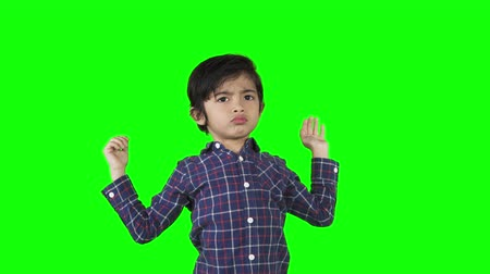 verwarring : Doubtful little boy shrugging shoulders while standing in the studio. Shot in 4k resolution with green screen background