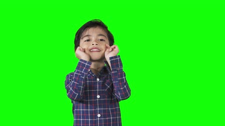 nevetséges : Funny little boy showing joking gesture while standing in the studio. Shot in 4k resolution with green screen background Stock mozgókép