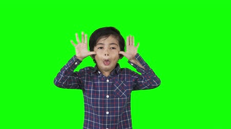 moqueries : Little boy showing a mocking or silly gesture in the studio. Shot in 4k resolution with green screen background