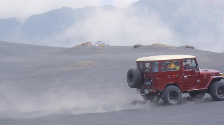erupção : EAST JAVA, Indonesia - August 12, 2019: Tourism jeep moving on the sea of sand at Mount Bromo national park during misty morning. Shot in 4k resolution